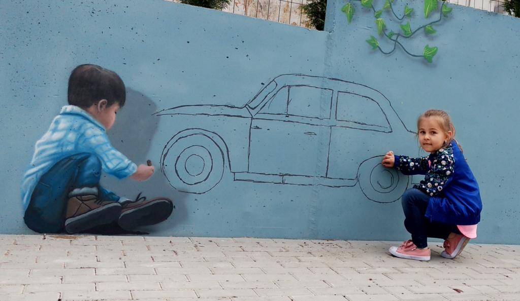 malowidło 3d na betonie, chłopiec rysuje samochód